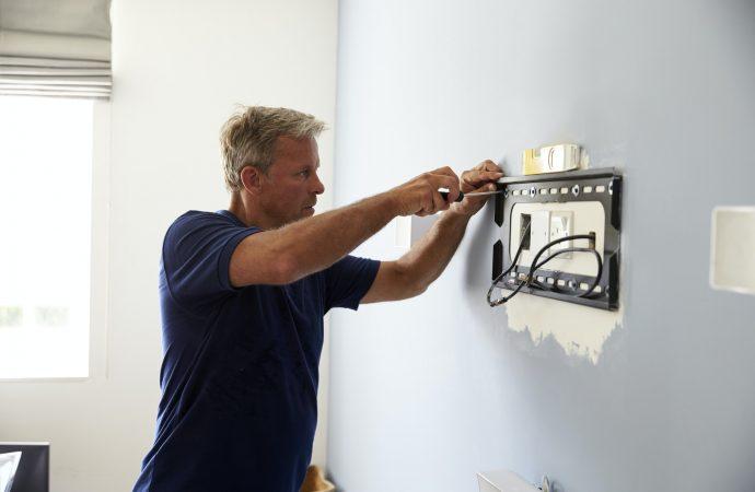 Man Fitting Bracket For Flat Screen TV Onto Wall